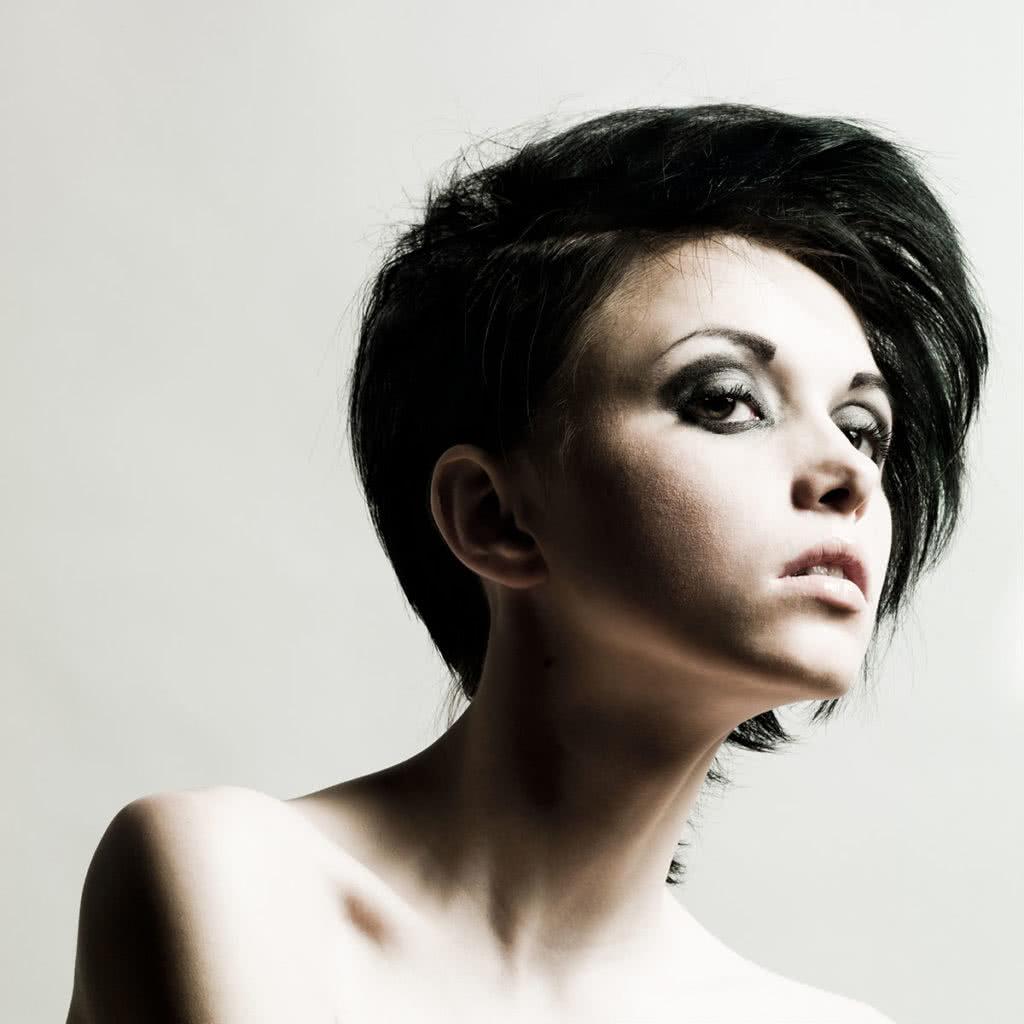 Krótka fryzura z czarnymi włosami i mocnym makijażem